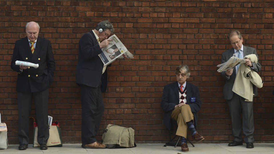 Men in suits read newspapers while standing against a brick wall