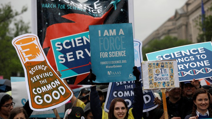 Demonstrators in Washington, D.C., hold signs that promote science