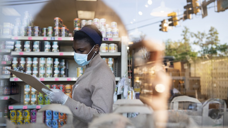 A cashier wearing a face mask, looking at a clipboard in a store