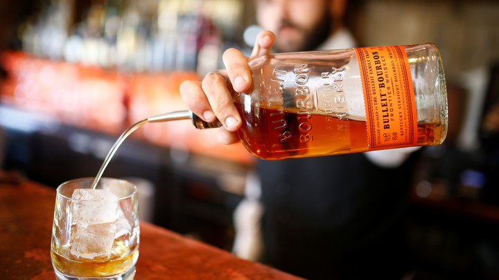 A bartender pours a glass of bourbon whiskey