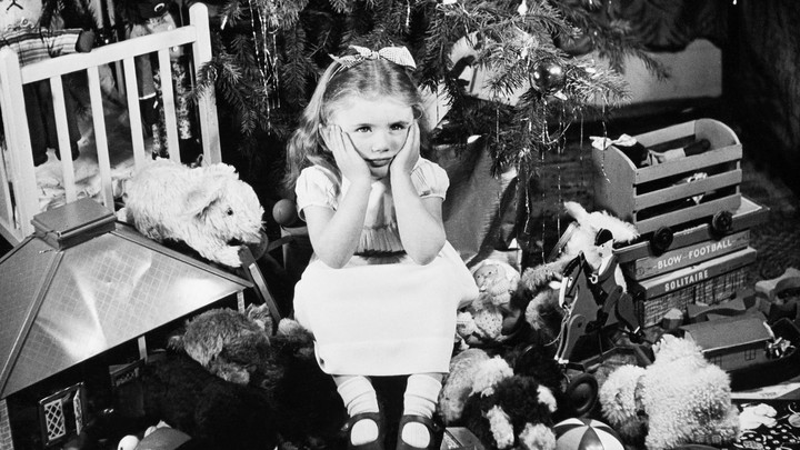 A girl sits with her face in her hands, looking disgruntled, surrounded by gifts under a Christmas tree