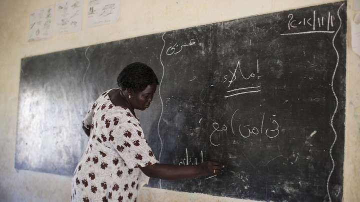 A mathematics teacher writes on the chalkboard at the Juba One Girls Basic Education School, in South Sudan, in 2012.