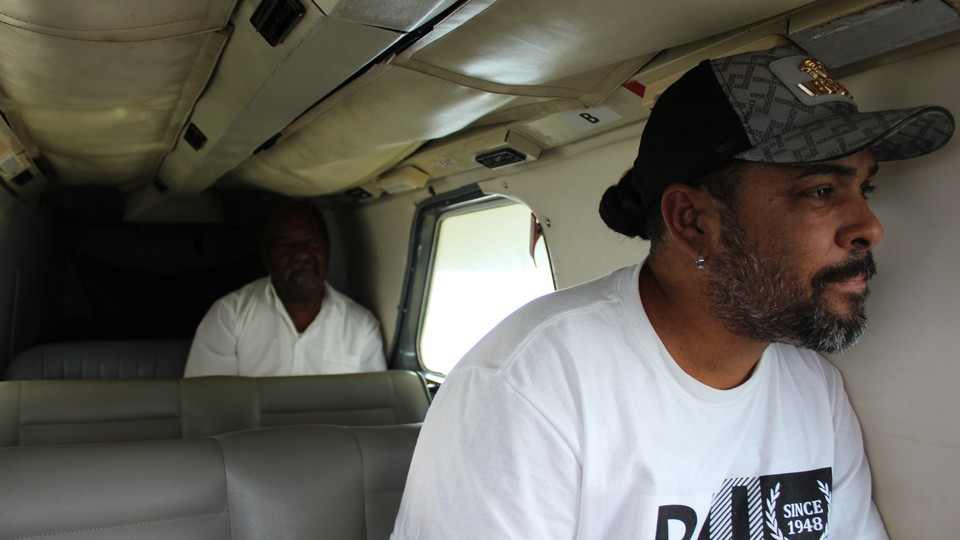 Two men sitting inside an airplane. One is looking out a window.