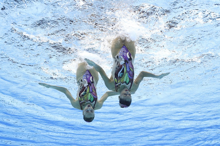 Two artistic swimmers float upside down during a routine, as seen from underwater.
