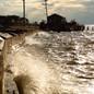 Water slams against a sea wall