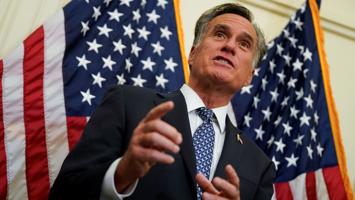 Mitt Romney stands in front of two American flags.