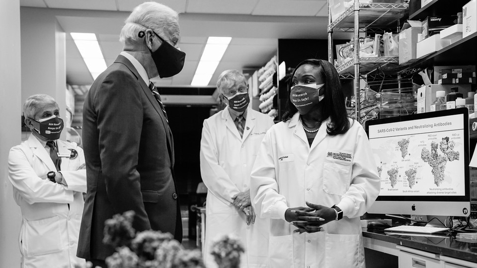 President Joe Biden listens to Kizzmekia Corbett, an immunologist with the Vaccine Research Center at the National Institutes of Health. Antony Fauci stands in the background.