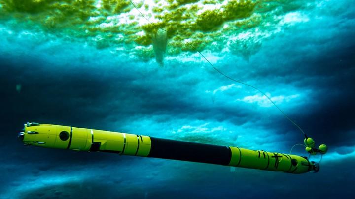 Icefin, a submersible robot, travels under Thwaites Glacier.
