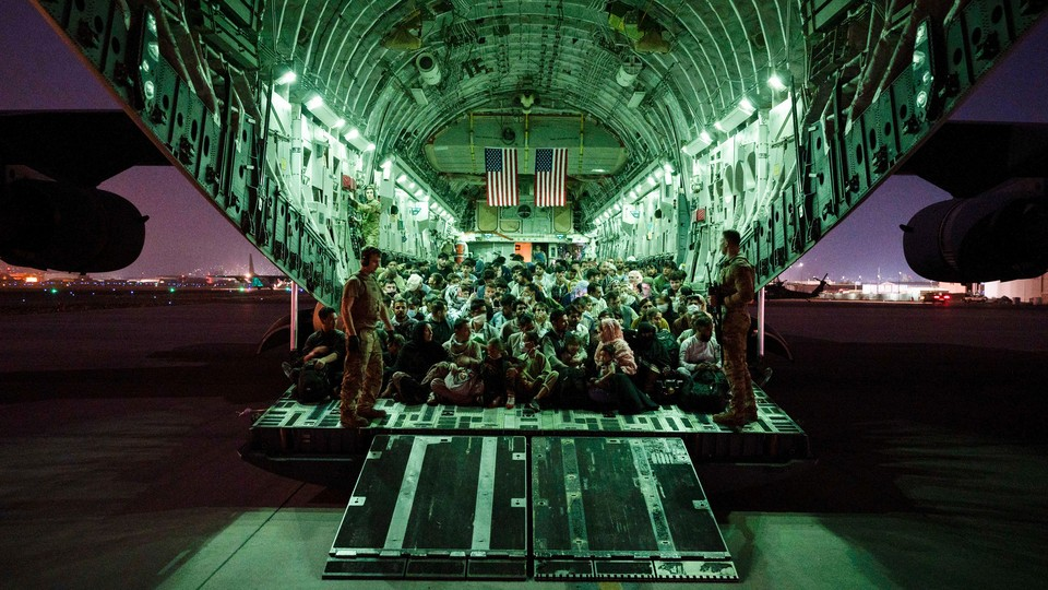 An aircrew assigned to the 816th Expeditionary Airlift Squadron assists evacuees aboard a C-17 Globemaster III aircraft in support of the Afghanistan evacuation.
