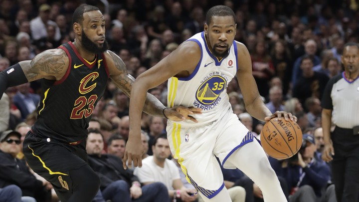 The Golden State Warriors' Kevin Durant goes to the basket against the Cleveland Cavaliers' LeBron James in the first half of Game 4 of basketball's NBA Finals on June 8, 2018, in Cleveland