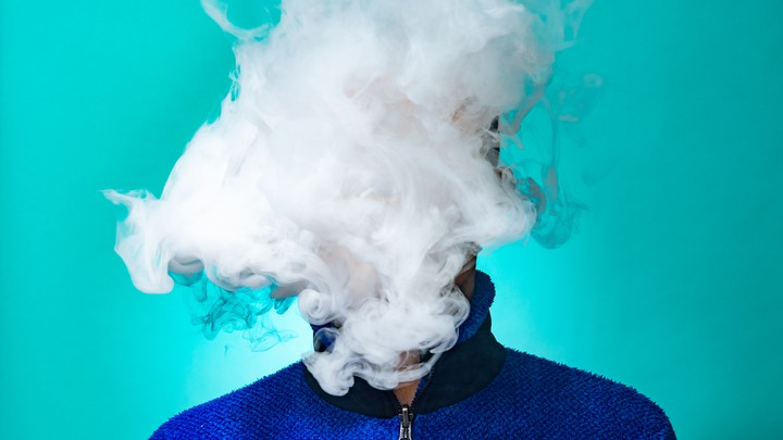 A person's face is obscured by a cloud of vapor.