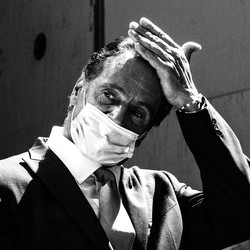 Andrew Cuomo wipes his hand across his forehead while wearing a mask