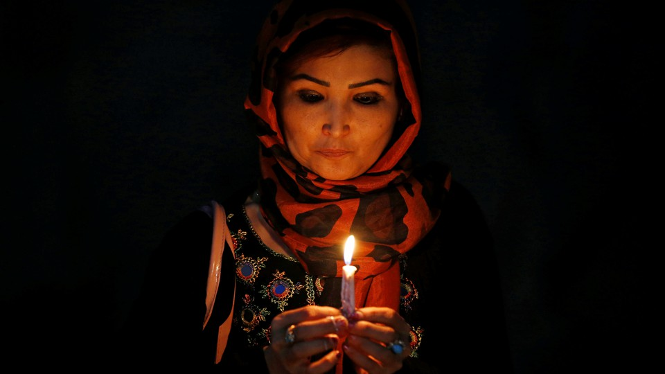 A woman holds a lit candle for the victims of Wednesday's blast in Kabul, Afghanistan.