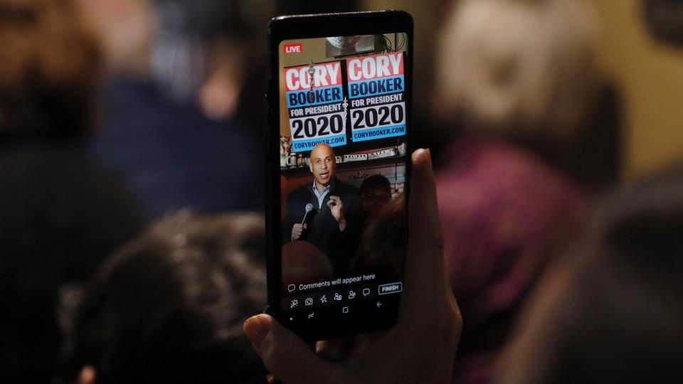 Cory Booker, seen through a cellphone, speaking in Marshalltown, Iowa