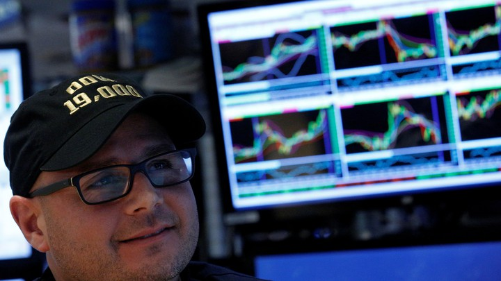 The specialist trader Mario Picone wears a Dow 19,000 hat on the floor of the New York Stock Exchange on November 22, 2016.