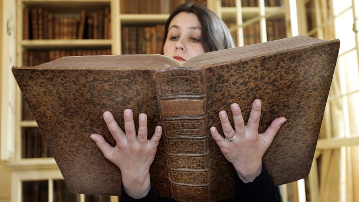 The curator of the museum at Samuel Johnson's house holds a copy of his first dictionary