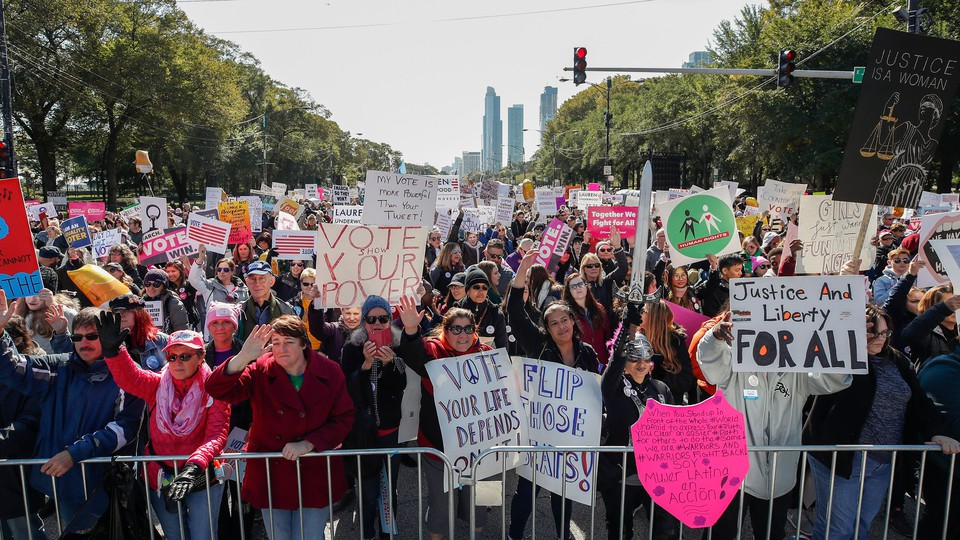 People hold signs during a rally and march at Grant Park on October 13, 2018, in Chicago, Illinois to inspire voter turnout ahead of midterm polls in the United States
