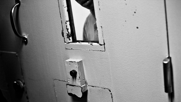 A person looking out of jail cell