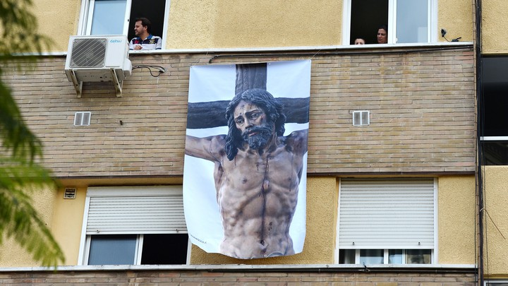A poster depicting a religious image of Jesus Christ hangs on a facade on April 8, 2020, in Seville, where Easter processions were cancelled during a national lockdown to prevent the spread of the COVID-16 disease.