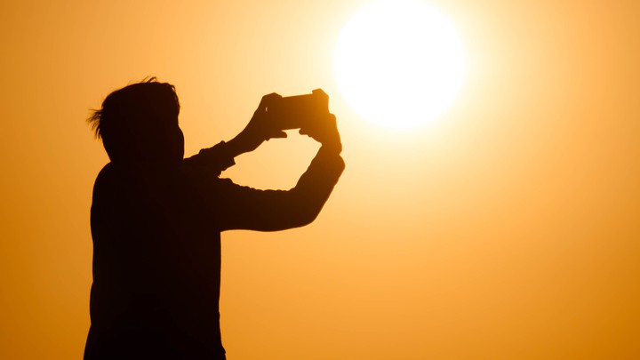 Silhouette of person taking picture with phone