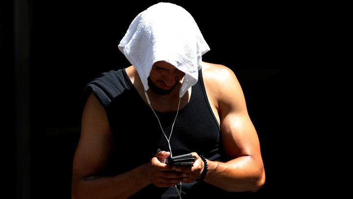 A man wearing a tank top covers his head with a towel and looks down at his phone.