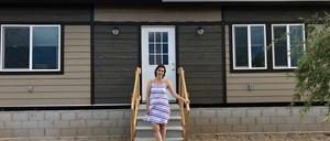 Elementary school teacher Sydney Scharer poses in front of her tiny home.