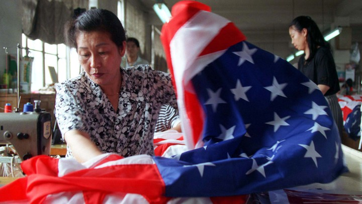A seamstress sews together an American flag at a factory in Beijing.