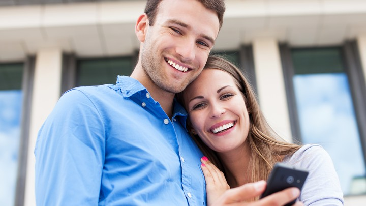 A couple embraces while using a cellphone.