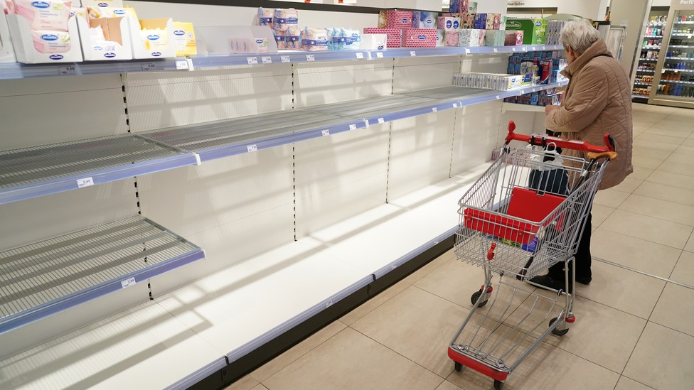 A woman shopping at a store with empty shelves