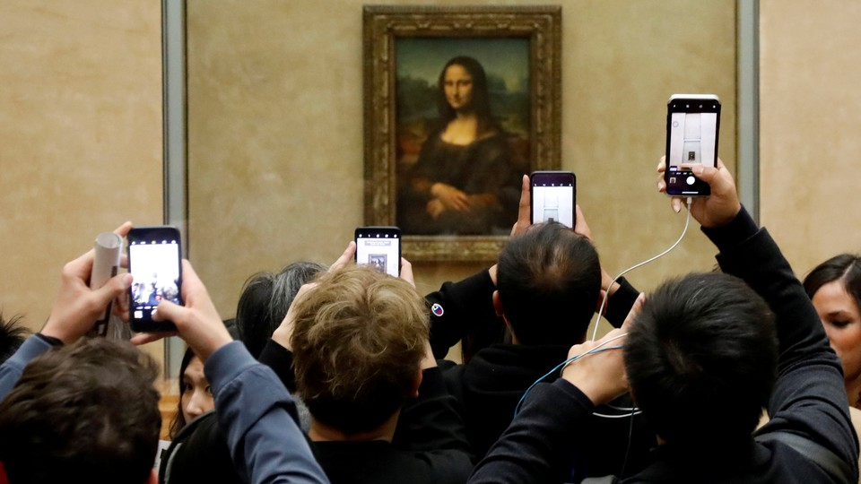 """A crowd of visitors taking pictures of the """"Mona Lisa"""" painting at the Louvre"""