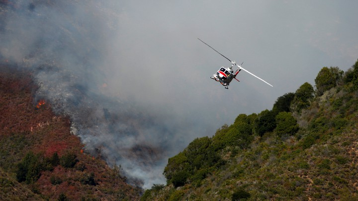 A Cal Fire helicopter flies over Garrapata State Park
