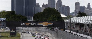 Cars race around a track in front of Detroit's skyline.