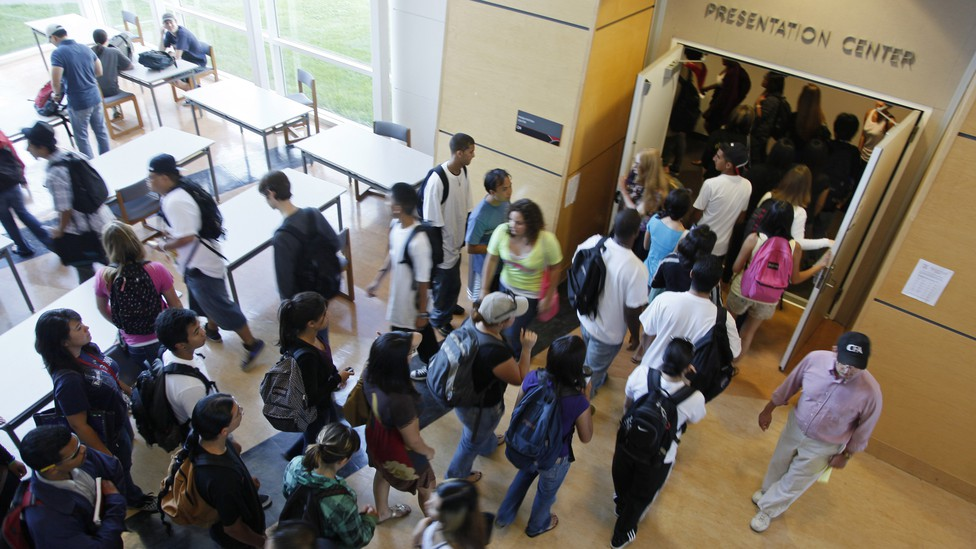 Students stand outside of a college lecture hall.