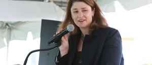 Alicia Glen speaks into a microphone at a podium inside a tent.