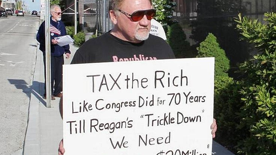 In this undated file photo, James Hodgkinson holds a sign during a protest outside of a U.S. Post Office in Belleville, Illinois.
