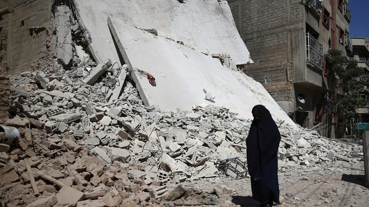 A woman walks past a damaged building after an airstrike in the rebel held Douma neighbourhood of Damascus.