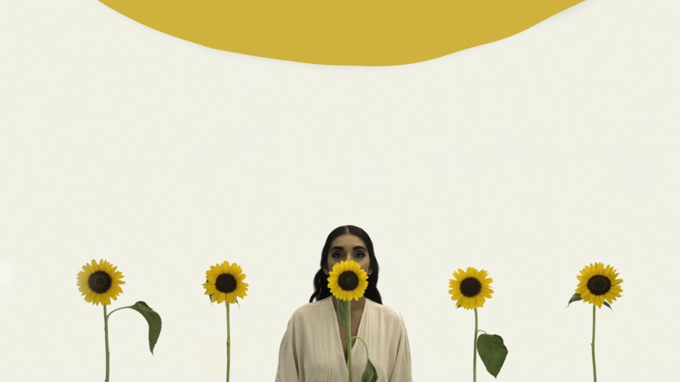Rupi Kaur poses with sunflowers.