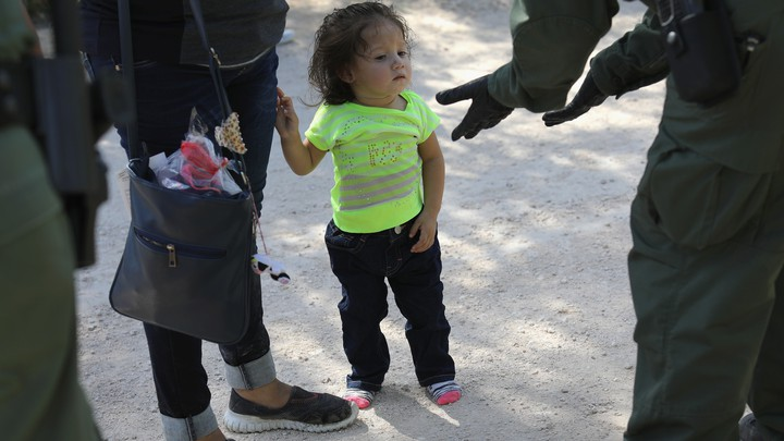 A small child looks at a border patrol agent as she and an adult, both asylum seekers, are taken into custody.