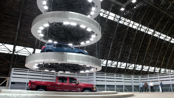 Cars on a large elevator as seen in a Chevrolet commercial