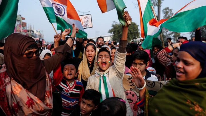 People hold signs and India's national flag during a protest in New Delhi, India.