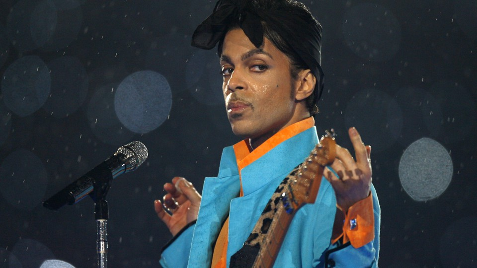 Prince standing at a microphone, holding a guitar, in the rain.