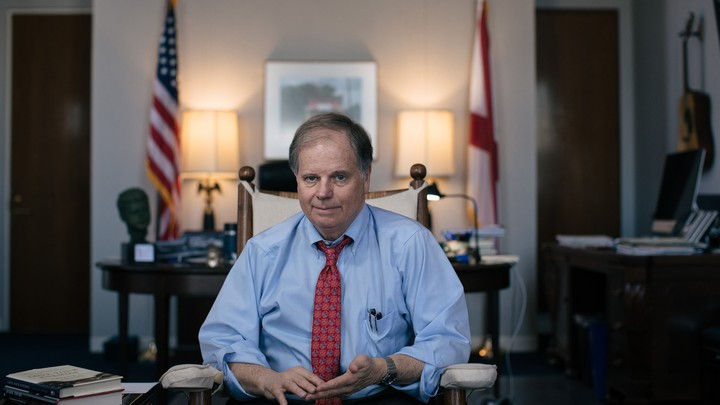 Framed by the U.S. and Alabama state flags, Doug Jones sits in an office.