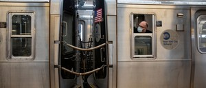 photo: A Metropolitan Transit Authority worker wearing a protective mask looks out the window of the subway as the F train departs Coney Island.
