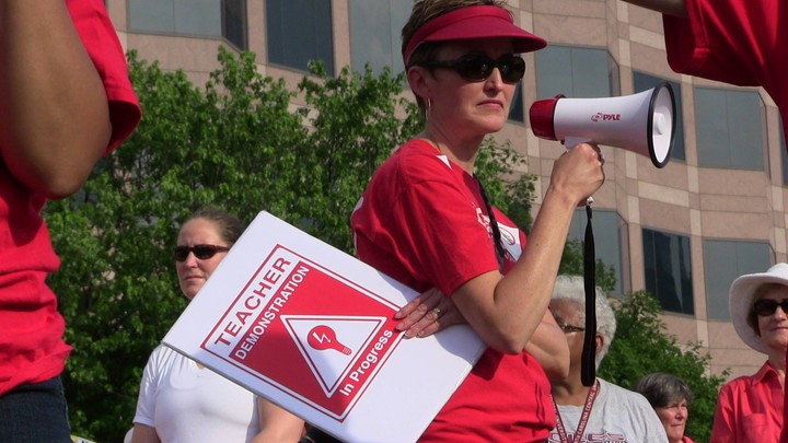 """Angie Scioli holds a megaphone and a poster that reads """"teacher demonstration in progress"""""""