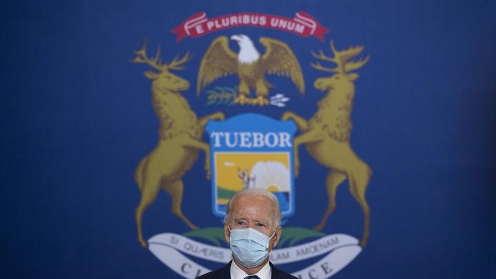 Joe Biden in front of the Michigan flag