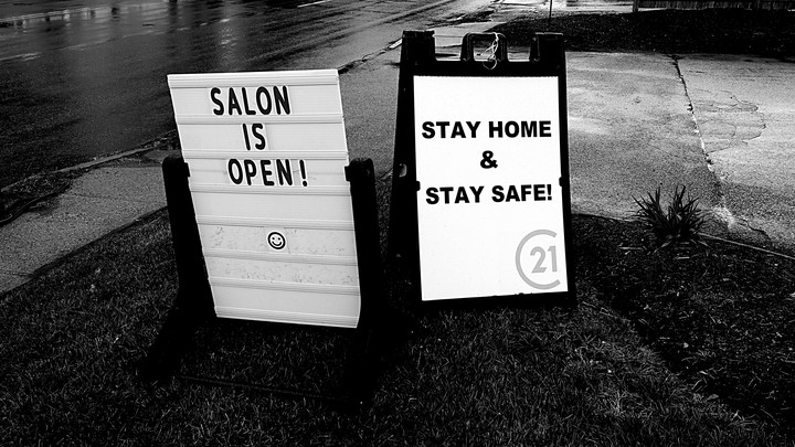 "A photo of two road-side signs. One says, ""Salon is open!"" The other says, ""Stay home and stay safe!"""