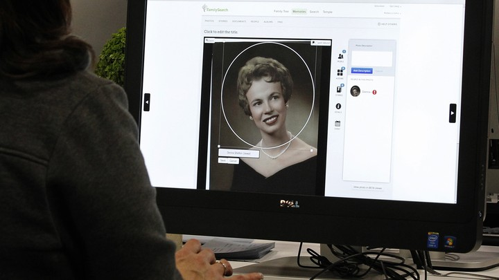 A person uses a computer to look at family history on a genealogy website.