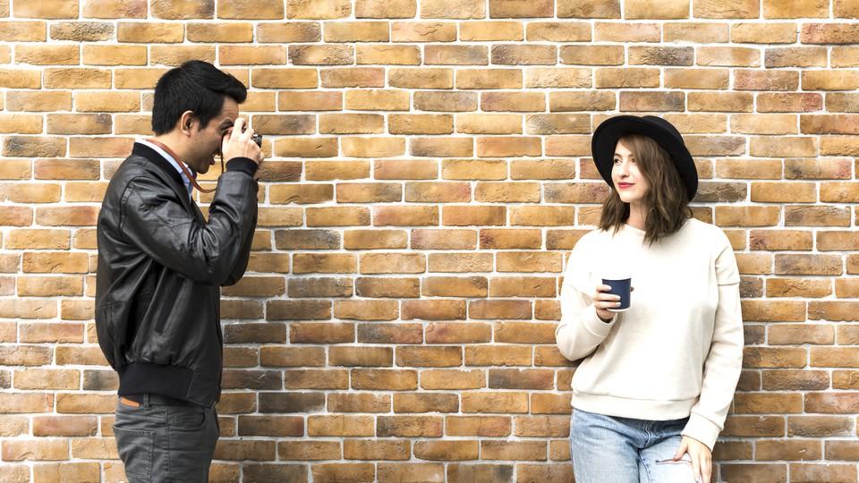 A man takes a photo of a woman against a brick wall.