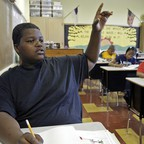 A black elementary student raises his hand in a majority black classroom.