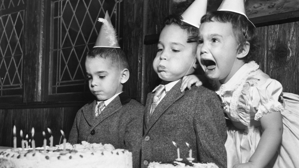 Three siblings with their birthday cake. One appears indifferent, one is blowing out the candles, one is crying.